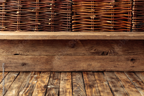 Obraz Old wooden table and a wicker fence. - fototapety do salonu