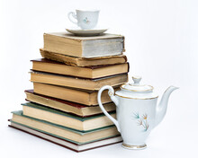 A Stack Of Old Books And An Elegant Coffee Set. On White Background.
