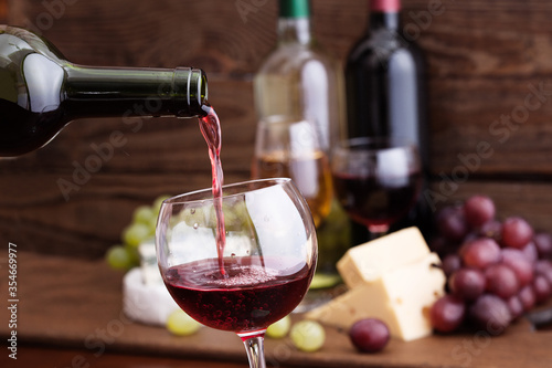 Fotografie, Obraz Red wine pouring into glass,  cheese and grape close-up.