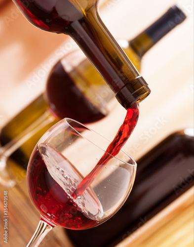 Fotografie, Obraz Red wine pouring into glass, close up.