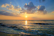 The atmosphere in the evening with the sunset. Shining against the sea surface Saw the waves tapping on the sandy beach