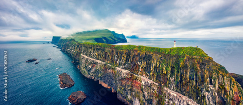 Fototapeta Panoramic view from flying drone of Mykines island with old lighthouse. Gloomy summer scene of Faroe Islands, Denmark, Europe. Stunning seascape of Atlantic ocean. obraz
