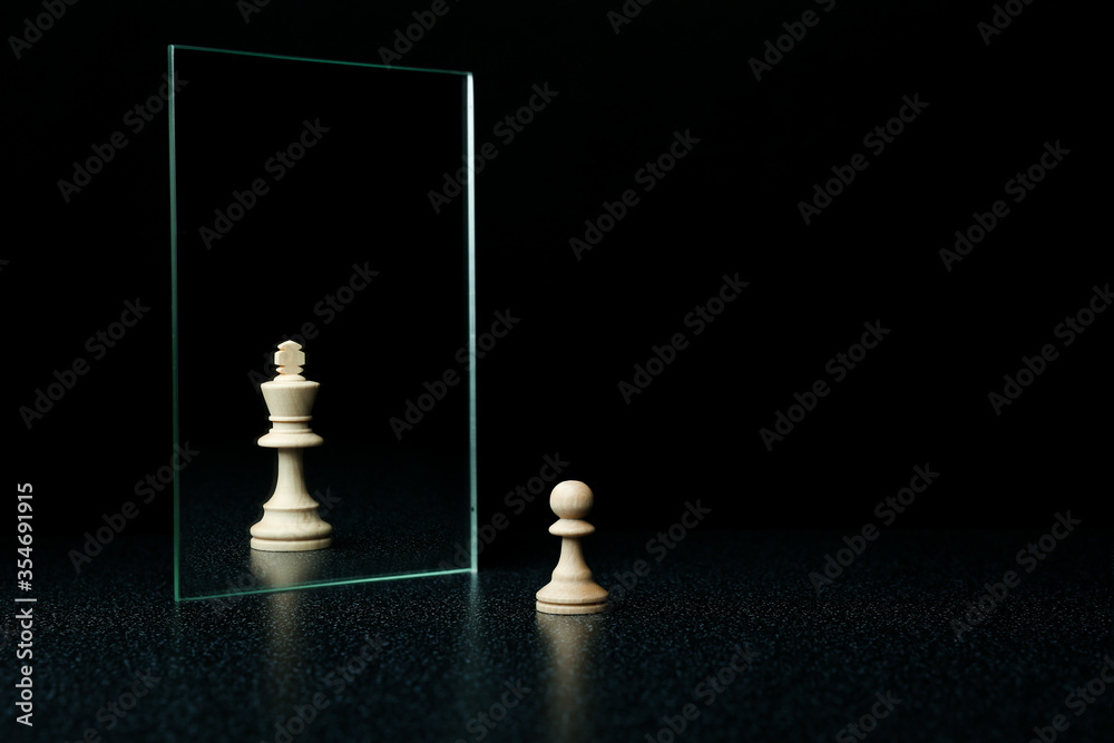 Fototapeta reassessment of their abilities. the pawn is reflected in the mirror like a king on black background