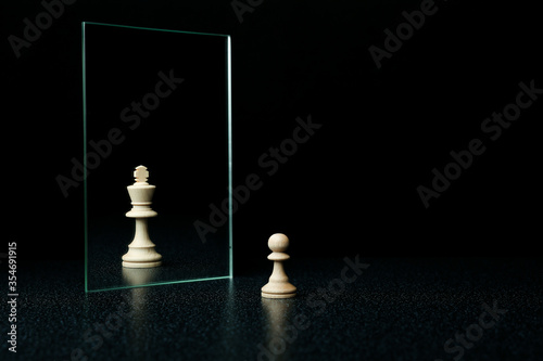 Obraz reassessment of their abilities. the pawn is reflected in the mirror like a king on black background - fototapety do salonu