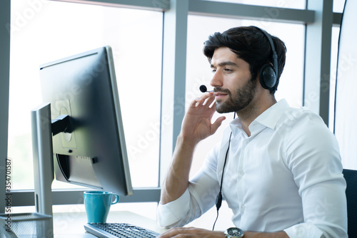 Obraz Smiling handsome young male call centre operator with headset.Confident male customer service representative,operator,agent,call centre worker,support staff speaking with head set in modern office - fototapety do salonu