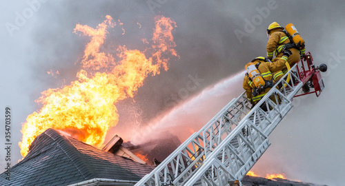 Firefighters battle blazing house fire. Canvas Print