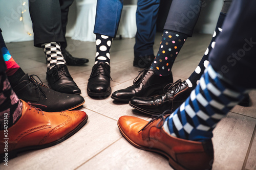 Fototapeta Close up of men legs wearing formal shoes and funny colorful socks. Seven friends feet in circle composition. obraz