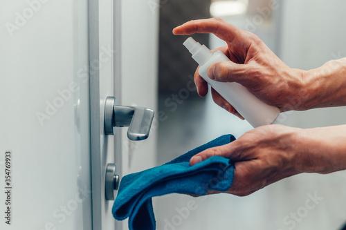 Fototapeta close up. employee spraying an antibacterial spray on the door handle. obraz