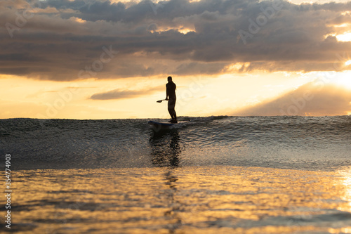 Fotografia Stand Up Paddle Boarding In Japan at Sunrise and Sunset a solo rider keeping fit & healthy on the Pacific Ocean in a black wetsuit, also catching some large waves, The ocean is blue with a nice sky
