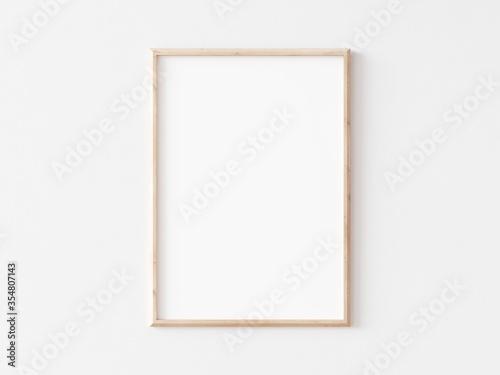 Cuadros en Lienzo Thin vertical wooden frame on white wall. 3d illustration.