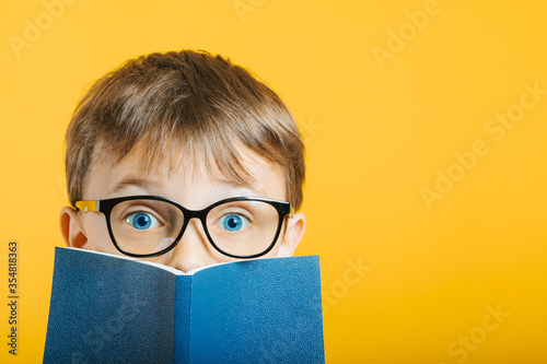Fototapeta child reads a book against a bright wall