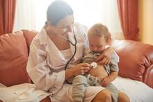 Woman Doctor Examining Toddler...
