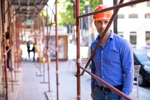 Fototapeta Uomo con camicia blue e casco arancione guarda serio mentre si trova sotto il po