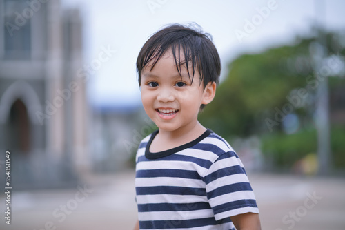 Obraz portrait of a boy looking and smiling to camera  - fototapety do salonu