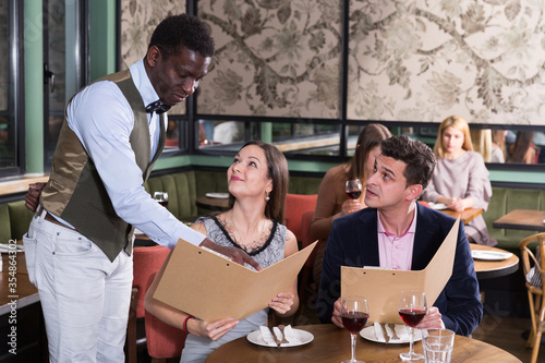 Fotomural African American waiter helping couple with menu