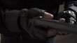Hands in black military gloves jerks the bolt and charges the gun