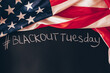 Hashtag Blackout tuesday inscription on a black background with american flag around. Black lives matter, blackout tuesday2020 concept. Toned.