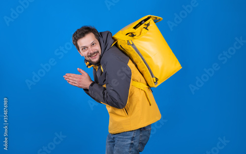 Fototapeta Emotional food delivery guy with grin on his face in yellow uniform and refrigerator bag on his back rubs his hands