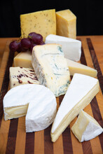 Different Cheeses Laying On Wooden Board. Brie, Camembert, Parmesan Collection. Studio Shot. Selective Focus. Front View. Dairy Food And Cooking At Home Concept For Flyers And Banners