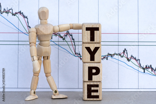 Fényképezés TYPE , the word is in cubes against a graph and a wooden person is standing next to him