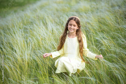 Fototapeta girl in a field. young woman in the field of flowers.  Beautiful girl walks in the park. Summer walks and relaxation. Smiling child. Daisies in the hands of a girl obraz