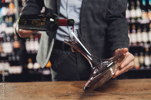 Sommelier pouring red wine into carafe decanter to make aeration drink Fototapeta