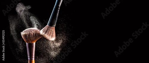 Fotografia Make up cosmetic brushes with powder blush explosion on black background