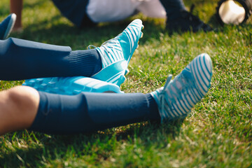 Kids on training session with roller foams. Children soccer football players stretching after workout training. Close-up image of soccer player legs with soccer socks, shin pads and cleats