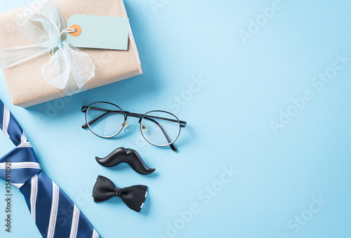 Fototapeta Happy Father's Day background concept with blue necktie, glasses, black mustache and gift box on bright pastel background with copy space for text. obraz