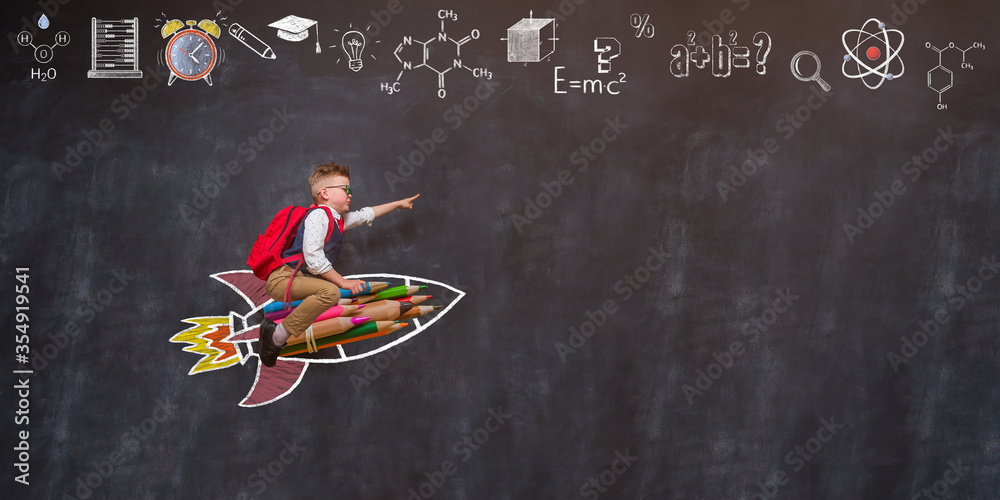Fototapeta Back to school. Boy flying on rocket from colorful pencils and pointing up.