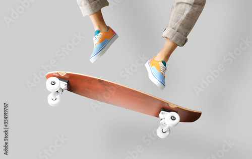 фотография Skateboarder in colored sneakers jumping on a skateboard