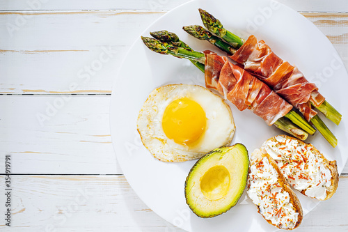 Fotografía fried asparagus wrapped in jamon, fried eggs, bruschetta with soft cheese and av