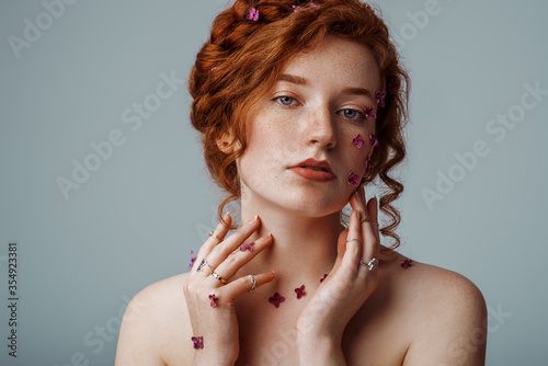 Fototapeta Beauty portrait of young beautiful  natural redhead girl with freckled skin, lilac flowers on her face, hair. Model wearing many rings. Copy, empty space for text obraz