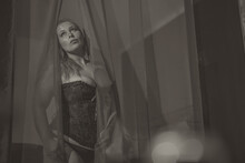 Woman In A Sexy Black Corset Or Bustier Going Through Transparent Or See Through Curtains In Front Of A Bed. Sexy Redheaded Curvy Woman In Lingerie Spreading Curtains And Looking Up
