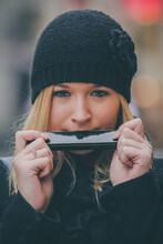 Frontal Portrait Of Young Attractive Blonde Woman Playing Harmonica On The Street. Woman Wearing A Black Hat, Jacket And Playing A Harmonica With Her Mouth With Eyes Opened Looking Into Camera.