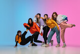 Group of dancers, boys and girls dancing hip-hop in stylish clothes on colorful gradient background at dance hall in neon. Youth culture, movement, style and fashion, action. Fashionable portrait.