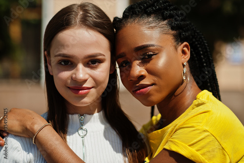 Close up faces of white caucasian girl and black African American together Fotobehang