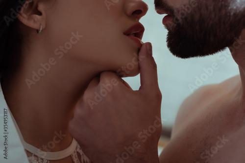 Fototapeta close up view of man touching lips of sexy young woman obraz