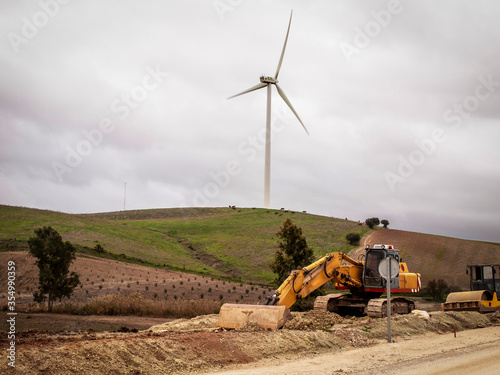 Photo Una excavadora trabajando cerca de un aerogenerador de energía eólica
