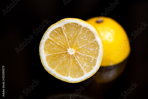 Lemon fruits are on top of the black kitchen table