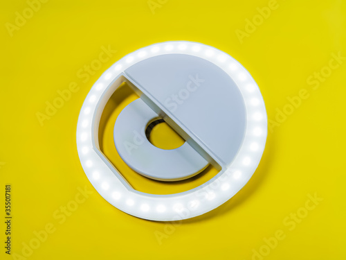 Fototapeta Close-up LED selfie circular ring light lamp on a yellow background