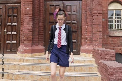 Female student teenager in uniform with backpack, building school background Fototapeta