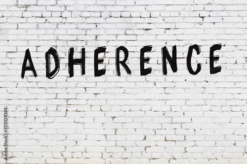 Photo Word adherence painted on white brick wall