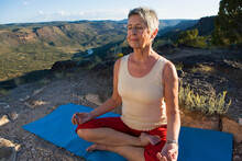 Senior Woman Practicing Yoga Overlooking Mountain Landscape, White Rock, New Mexico