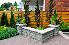 A Retaining Wall With Natural Stone Coping And Pillars Added Additional Seating For Entertaining In This Small Urban Backyard Garden.