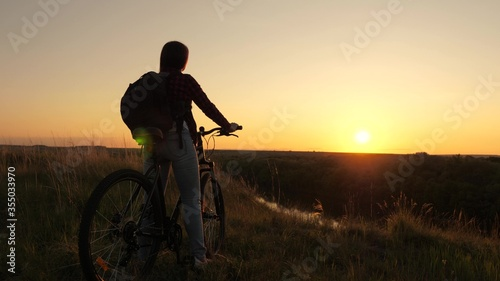 Foto Hiker healthy young woman rides a bicycle to edge of hill, enjoying nature and sun