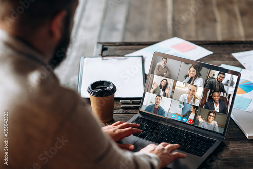 Obraz App for communication with employees. Online video conference. Young bearded man communicates via video call with business partners, he sits at the creative modern office space - fototapety do salonu