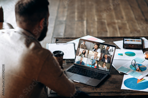 Obraz App for communication with employees. Online video conference. Young bearded man communicates via video call with colleagues, he sits at the creative modern office space - fototapety do salonu