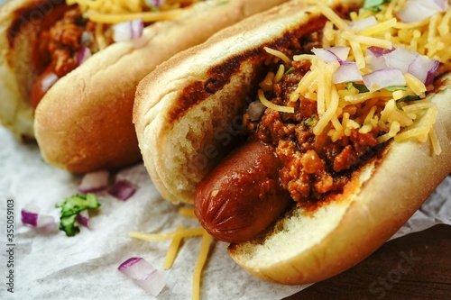 Homemade Chili dogs topped with cheddar cheese, selective focus Wallpaper Mural