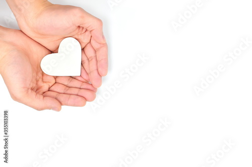 Photo Cupped hands holding a white heart in white background